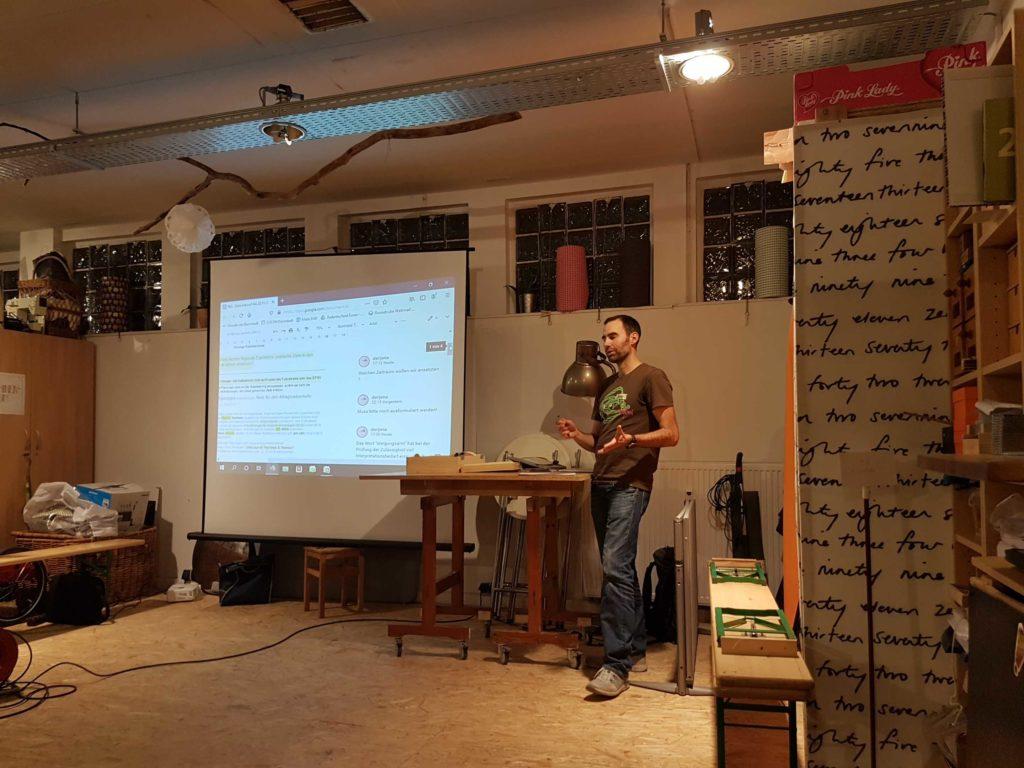 Man kann Jona auf der Bühne sehen, wie er uns seine Arbeit erläutert. Im Hintergrund auf der Leinwand ist die aktuelle Arbeitsversion des Zieledokuments zu sehen. Man erkennt viele Überarbeitungen und Kommentare darauf.