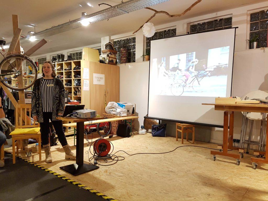 Klara steht auf der Bühne und präsentiert den neuen Interessierten den RadEntscheid Essen. Auf der Leinwand sieht man ein Bild mit radfahrenden Menschen.