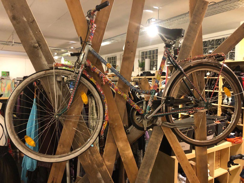 Ein wunderschön bunt lackiertes Fahrrad, das zu dekorativen Zwecken an einem aus sich überkreuzenden Holzlatten besthenden Raumtrenner hängt