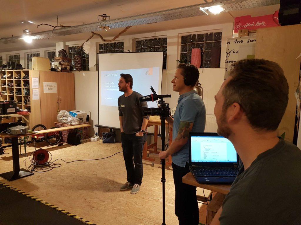 Auf einer kleinen Bühne steht Rafi, der Moderator des Abends und spricht. Im Hintergrund die Leinwand mit einer Powerpointfolie. Rechts steht ein Reporter vom WDR der den Abend dokumentiert. Ganz rechts sitzt Björn und führt Protokoll.