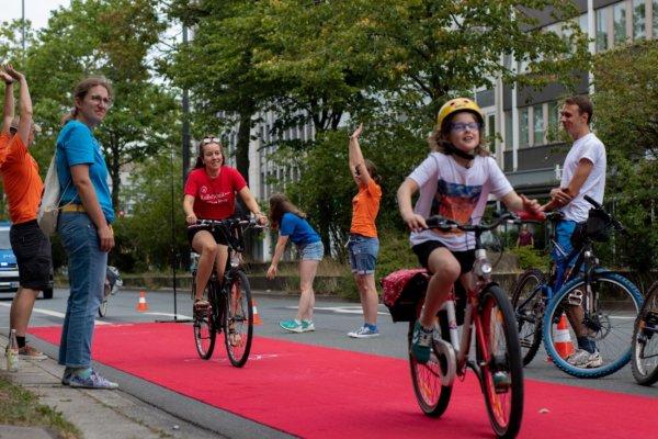 Zu sehen sind 2 Radfahrer (ein Erwachsener und ein Kind), die auf dem Roten Teppich fahren. Am Rand stehen jubelnde Aktive vom REE.